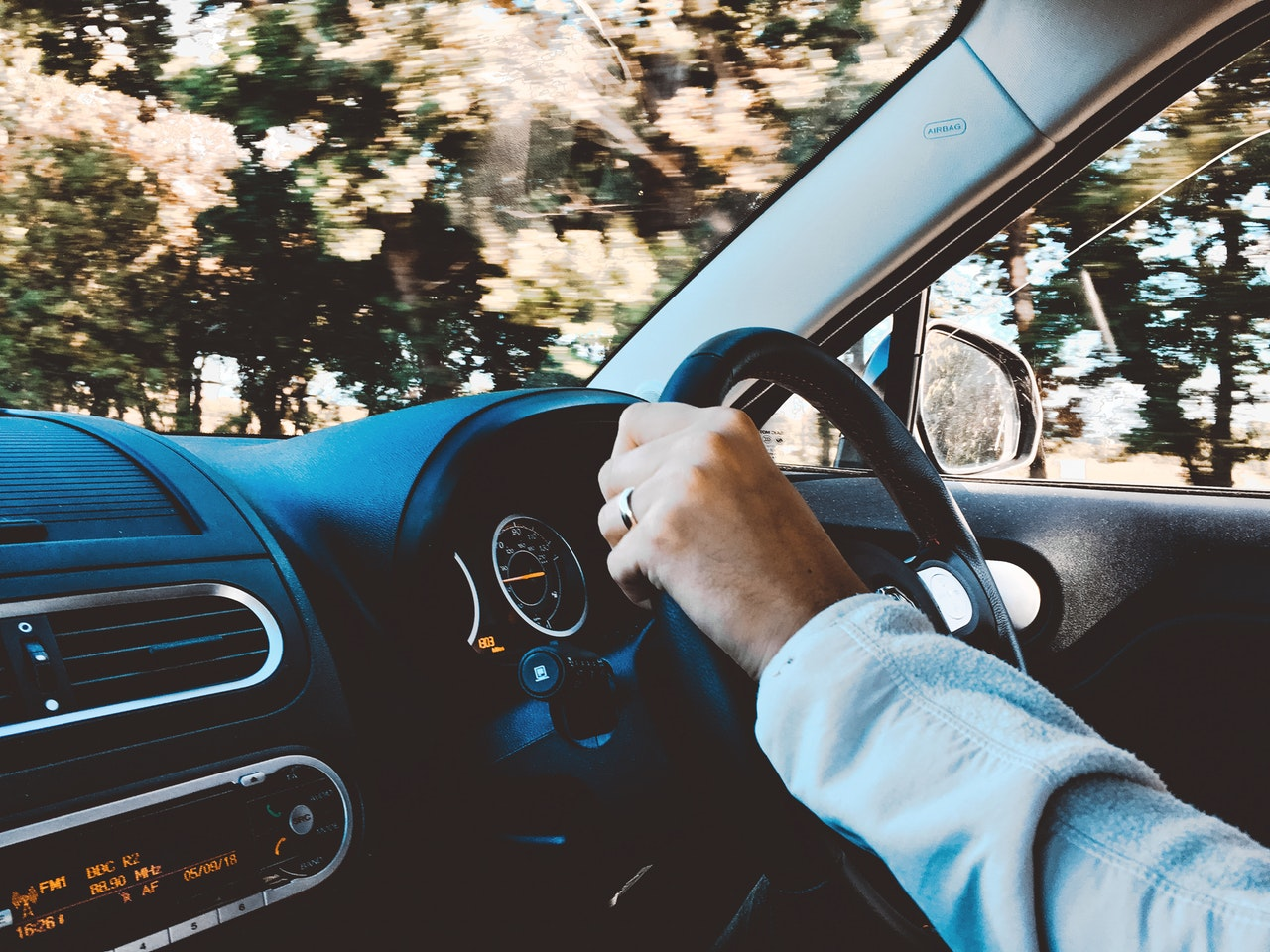 man with his hand on a steering wheel of a car